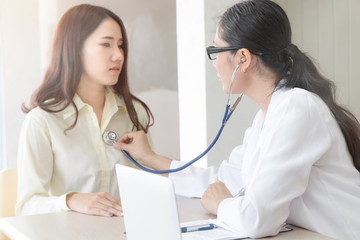 Female doctor is examining female patient using a stethoscope in the hospital. Healthcare and Medical concept.