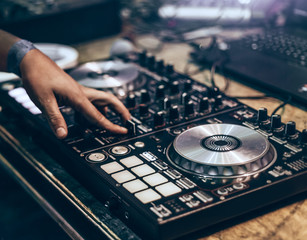 Dj mixing music track by hand on turn table