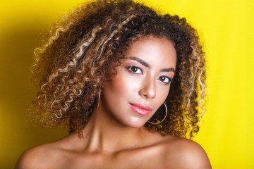 Beauty portrait of young african american girl with afro hairstyle. Girl posing on yellow background, looking at camera.