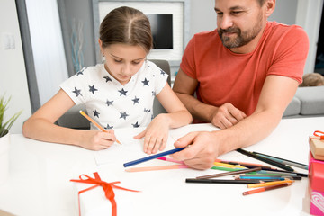 Portrait of bearded father helping little girl drawing handmade card for mothers day at home in modern living room