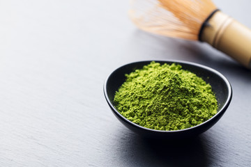 Matcha, green tea powder in black bowl with bamboo whisk on slate background. Copy space.