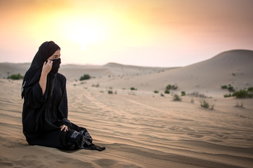 Beautiful Muslim woman sitting on sand in the desert during magnificent sunset.