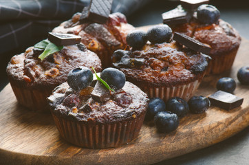 Fresh, blueberry muffins with strawberry, chocolate on a wooden board and stone background with sugar and fruits. Food background. Concept of pastry.