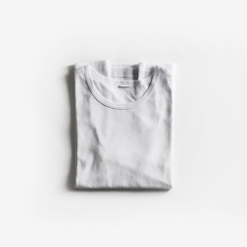 Tshirt template for your design. Folded blank white t-shirt on white paper background. Flat lay.