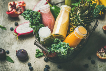 Colorful smoothies in bottles with fresh tropical fruit and greens in basket on grey concrete background, selective focus. Healthy, vegetarian, detox, dieting, clean eating breakfast food concept