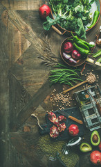 Wall Mural - Winter vegetarian, vegan food cooking ingredients. Flat-lay of seasonal vegetables, fruits, beans, cereals, kitchen utencils, dried flowers, olive oil over wooden background, top view, copy space