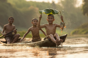 Asia children enjoying in boat on beautiful river