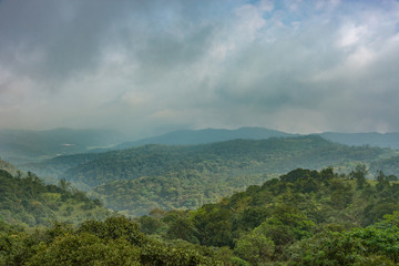 Talakaveri, India - October 31, 2013: Blue and gray clouds over the green jungle covered highlands around the spring of the Kaveri River sanctuary.