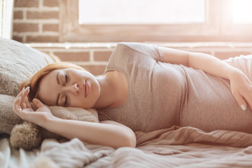 Beautiful pregnant woman laying on bed resting