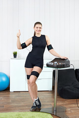 Beautiful girl posing in a fitness room next to a muscle stimulation machine.