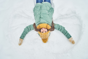 Beautiful young girl lying in the snow. making a snow angel