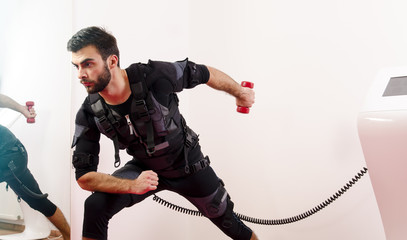 Man in Ems suit exercising triceps