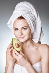 portrait of a young girl with healthy and silky skin, with a white towel on her head holding an avocado slice with a stone. concept of healthy food.