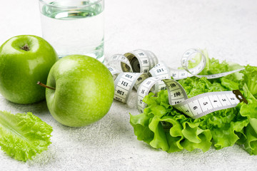 Healthy food. Green apple, lettuce salad, glass of water, measuring tape on white background. Dieting, slimming, healthy eating concept