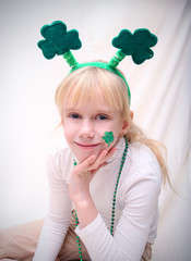Blonde little girl with the Saint Patric's day symbols: clover leaf and green hat