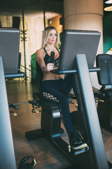 beautiful blonde woman smiling in the gym working out cycling in a cycle machine