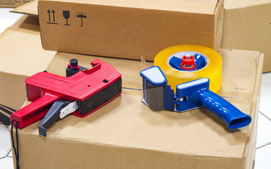 Packing tape dispenser and label gun on the cardboard box.