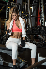 woman resting sweating with towel and water in the gym