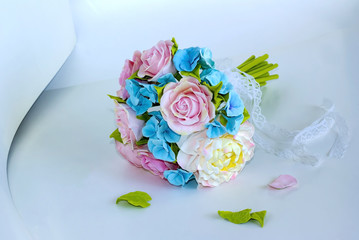 delicate bouquet of pink and blue flowers with a lace ribbon on a light background