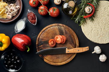 Cutting wooden board with traditional pizza preparation ingredients: cheese, tomatoes, sauce, olives, olive oil, pepper, spices. Black texture table background