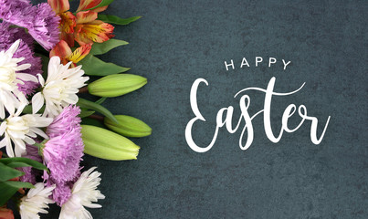 Spring season still life with Happy Easter calligraphy holiday script over dark blackboard background texture with beautiful colorful white, pink, orange, purple and green flower blossom bouquet