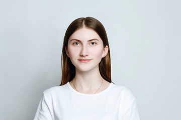 Model portrait without make-up in a white t-shirt on a white background. The girl poses in studio, smiling looking at camera. close up