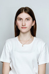 Model portrait without make-up in a white t-shirt on a white background. The girl poses in studio, looking at camera with serious or pensive expression. close up