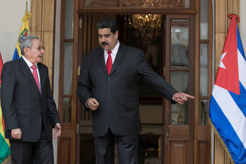 Venezuela's President Nicolas Maduro talks with Cuba's President Raul Castro during the welcoming ceremony of an ALBA-TCP alliance summit in Caracas