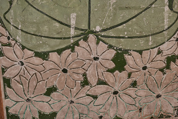 Close up of old chipped wall with green and white flowers for background