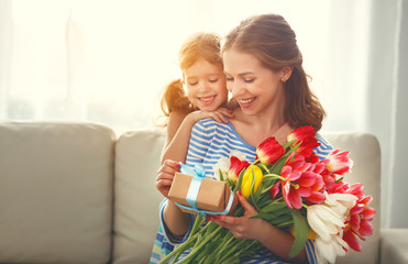 happy mother's day! child daughter   gives mother a bouquet of flowers to tulips and gift.