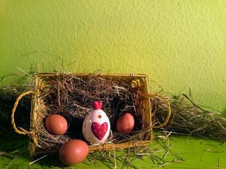 Osterkorb gefüllt mit Heu und braunen Eiern und einem Deko-Huhn mit grünem Hintergrund