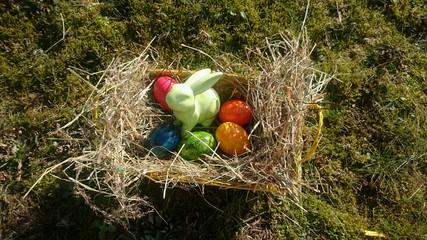 Osterkorb mit bunten Eiern und Osterhasen aus Porzellan
