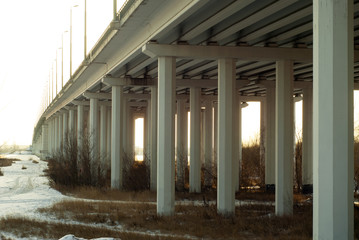 view from below on concrete supports of an automobile bridge across a floodplain river valley in autumn..