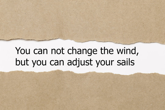 Motivational quote You can not change the wind but you can adjust your sails, appearing behind torn paper.