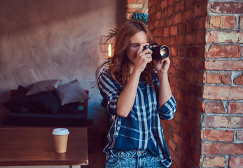 Young charming girl photographer stands in a room with a loft in