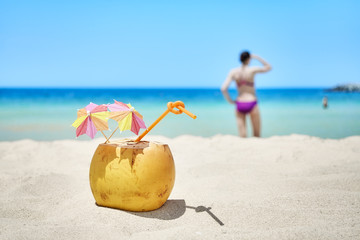 Coconut with colorful umbrellas and straw on a beach, summer holiday concept, selective focus.