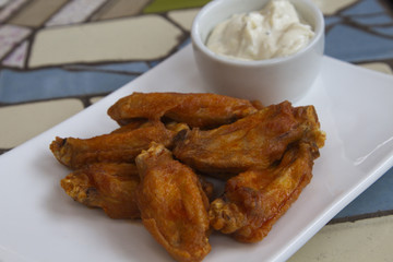 Hot chicken wings with blue cheese dipping sauce in casual presentation