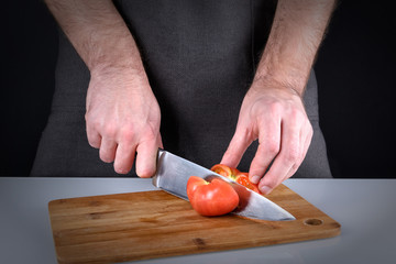 Photo of the cooking process. A man cuts a tomato with a sharp knife. Picture with a vignette.