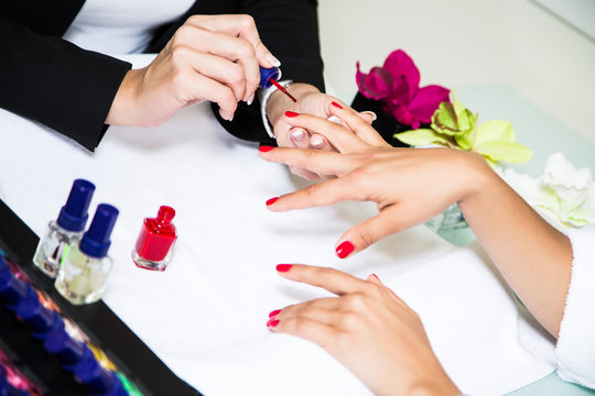 мастер делает маникюр клиентке. руки с красным маникюром на фоне флаконов лака для ногтей