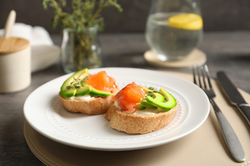 Delicious bruschettas with salmon and avocado on plate