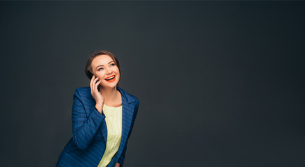 laughing business woman talking on her smart phone looking away while standing against grey background. Happy talking on the phone