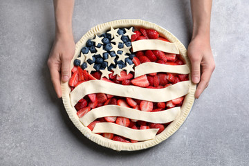 Woman with American flag pie on grey background