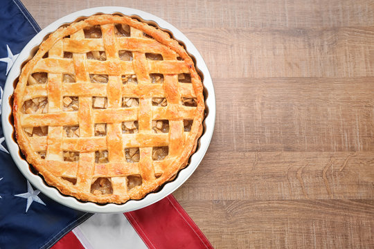 Delicious American apple pie with flag on table