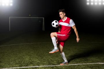 Soccer player juggling football on field