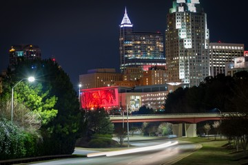 A night cityscape scene of colorful downtown Raleigh, North Carolina with traffic light trails.