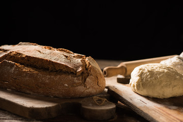Freshly baked bread on wooden table on dark background