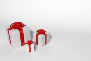 drei weiße geschenkkartons mit roter schleife