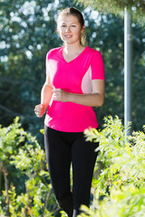 Sportswoman in pink T-shirt is jogging
