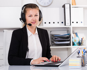 Young dispatcher woman in black suit is talking by headset with client