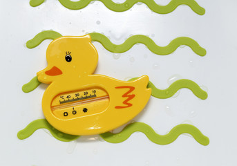 Funny yellow duck thermometer for meashurement of water temperature during newborn baby bath in a bathtub for child